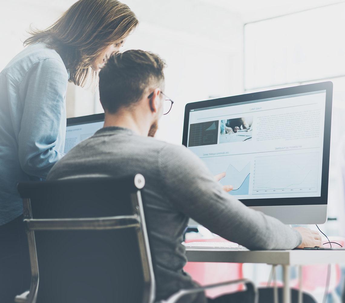 Deux collègues discutant des informations présentés à l'écran de l'ordinateur